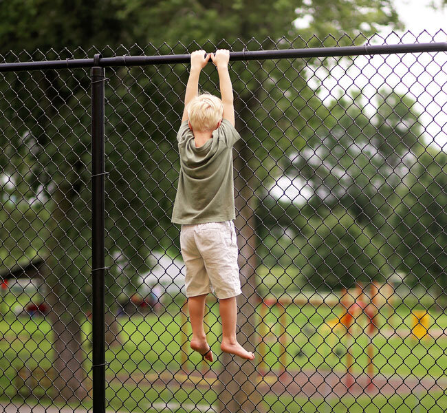 Child handing from a fence